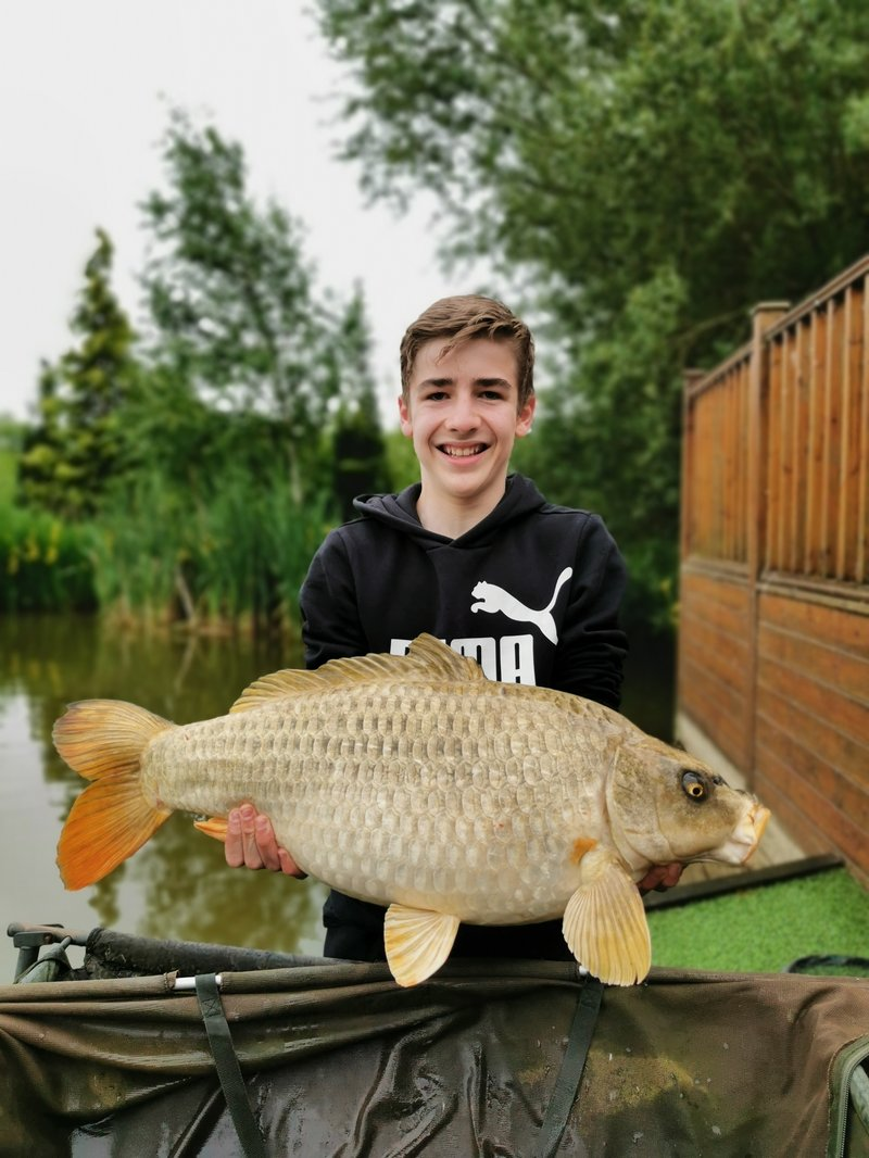 Joshua Rose playing a  Cherry Springs Carp from the decking of Pochard Lodge